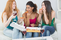 Happy young female friends eating pizza with wine on sofa at home