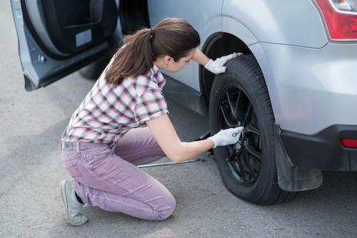 women changing tire on car
